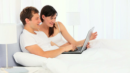 Happy young couple using a laptop Footage