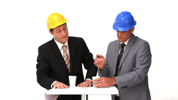 Two architects with safety helmets speaking Footage