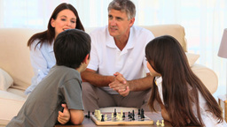 Parents looking at their children playing chess Footage