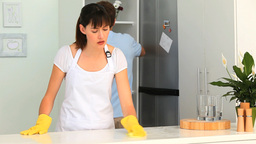 Woman cleaning her kitchen with her boyfriend Stock Video Footage