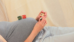Pregnant woman playing with building blocks Footage
