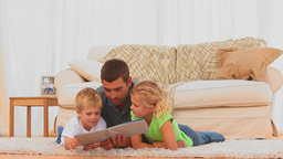 A father reading a book with his children Footage