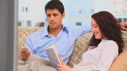 Man watching tv while his girlfriend is reading a  Footage