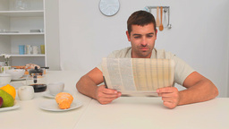 Man reading his newspaper in the kitchen Footage