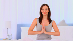 Peaceful woman practicing yoga on her bed Stock Video Footage