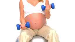 Pregnant woman doing exercises against a white bac Stock Video Footage