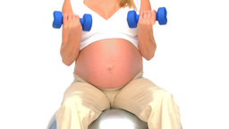 Pregnant woman doing exercises against a white bac Footage