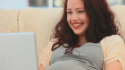 Pregnant woman chatting on her laptop Footage