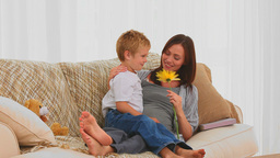 Little boy offering a flower to his pregnant mothe Stock Video Footage