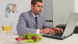 Businessman working on his laptop at lunch time Footage