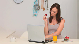 Woman eating strawberry in front of her laptop Stock Video Footage