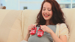 Pregnant woman holding little red shoes Footage