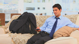 Tired businessman after work sitting on his sofa Stock Video Footage