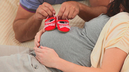 Future parents holding little red shoes Footage