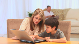 Grandmother with her grandson using a laptop Footage