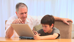 Grandfather and his grandson using a laptop Stock Video Footage