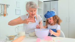 Grandmother and grand daughter baking together Footage