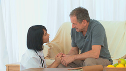 Asian nurse talking with her patient Footage
