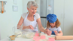 Grandmother and her grand daughter cooking togethe Stock Video Footage