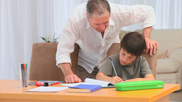 Grandfather helping his grandson to do homeworks Stock Video Footage