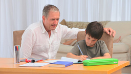 Grandfather helping his grandson to do homeworks Footage