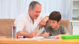 Little boy doing homeworks with his grandfather Footage