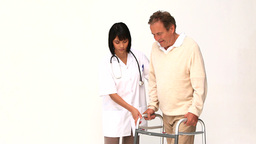 Nurse helping her patient to walk Stock Video Footage