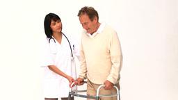 Nurse helping her patient to walk Footage