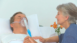 Elderly woman talking to her unconscious husband Footage