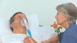 Elderly woman talking to her unconscious husband Stock Video Footage