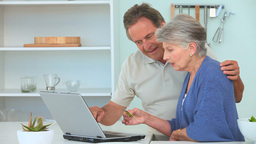 Elderly couple paying something on internet Stock Video Footage