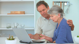 Elderly couple paying something on internet Footage