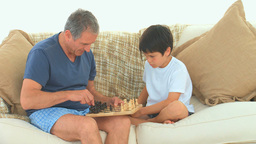 A boy playing chess with his grandfather Footage