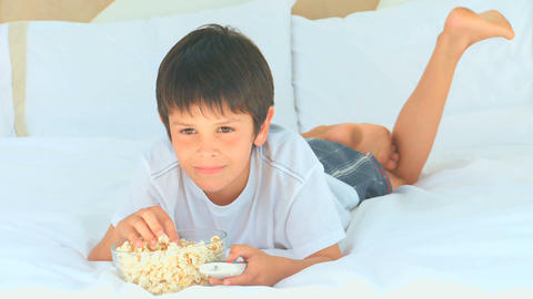 A little boy eating popcorn in front of the tv Footage