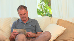 Retired man reading a newspaper Stock Video Footage