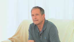 Retired man sitting and looking at the camera Stock Video Footage