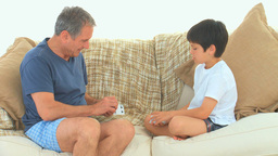 A boy playing cards with his grandfather Footage
