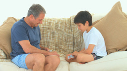 A boy playing cards with his grandfather Stock Video Footage