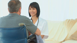 A patient in wheelchair talking with his nurse Footage