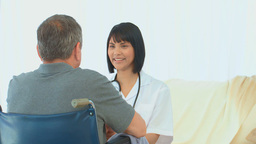 A patient in wheelchair talking with his nurse Stock Video Footage