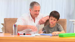 A man hepling his grandson to do his homeworks Stock Video Footage