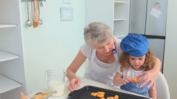 Grandmother and her grand daughter trying cookies Footage