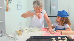 Grandmother teaching how to bake to her grand daug Stock Video Footage
