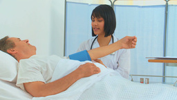 Asian nurse taking the blood pressure of her patie Stock Video Footage