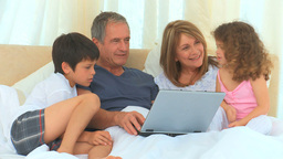 Family laughing in front of laptop Footage