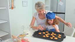 Grandmother and her grand daughter enjoying cookie Footage