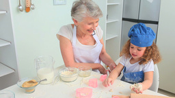 Cute curlyhaired girl baking with her grandmother Footage
