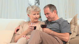 Lovely retired couple enjoying a glass of red wine Footage