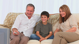 Family laughing in front of the tv Footage