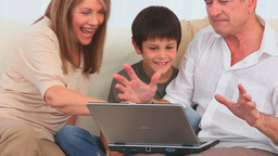 Family using a laptop to play a game Footage